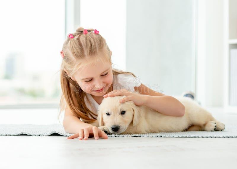 Little girl hugging retriever puppy. Cute little girl hugging retriver puppy at home stock photography