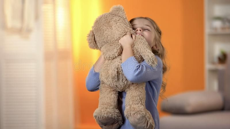 Cute little girl hugging teddy bear, favorite toy, happy childhood, best present royalty free stock photography