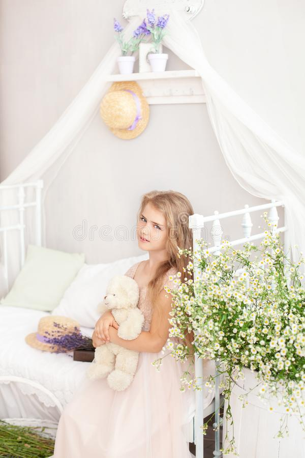 Cute little girl hugs a teddy bear, looks at the camera and smiles, sitting at home on the bed and with a bouquet of field daisies. Concept of childhood, toys royalty free stock photos