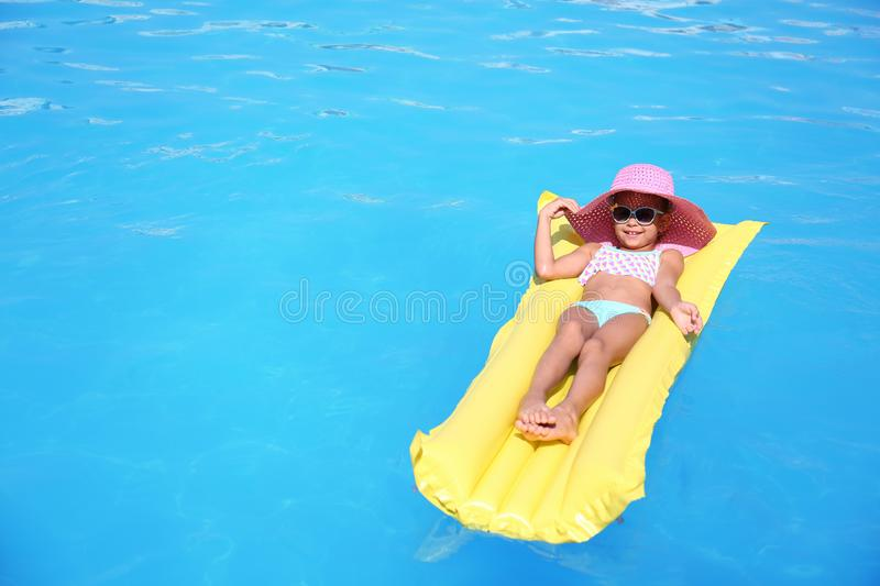 Cute little girl on inflatable mattress in pool royalty free stock photos