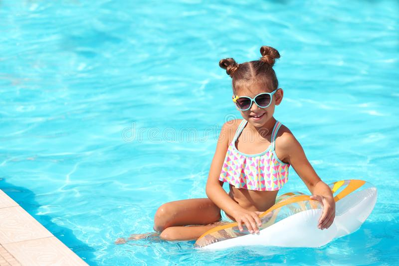 Cute little girl with inflatable ring in pool stock photography