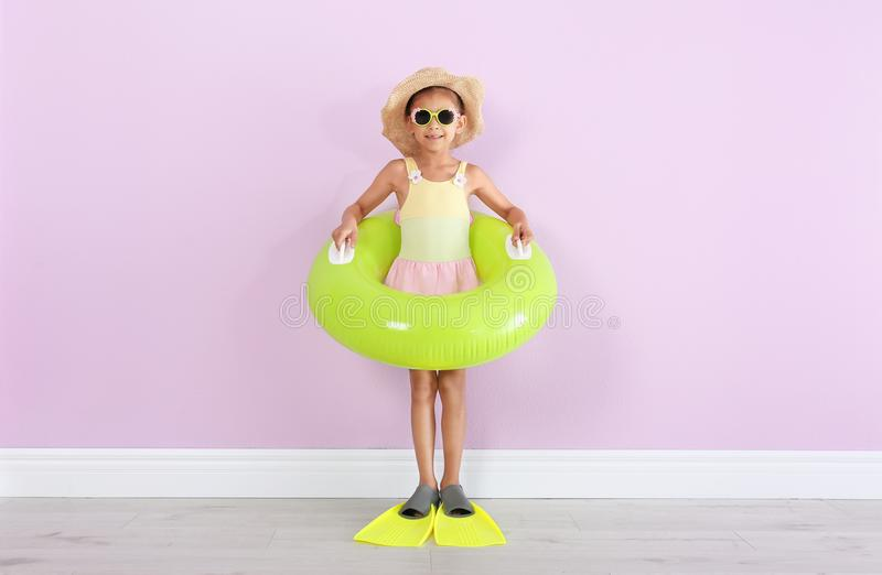 Cute little girl with inflatable ring wearing flippers. Near color wall royalty free stock photo