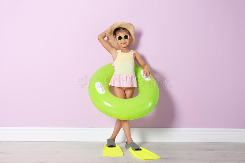 Cute little girl with inflatable ring wearing flippers. Near color wall stock photography
