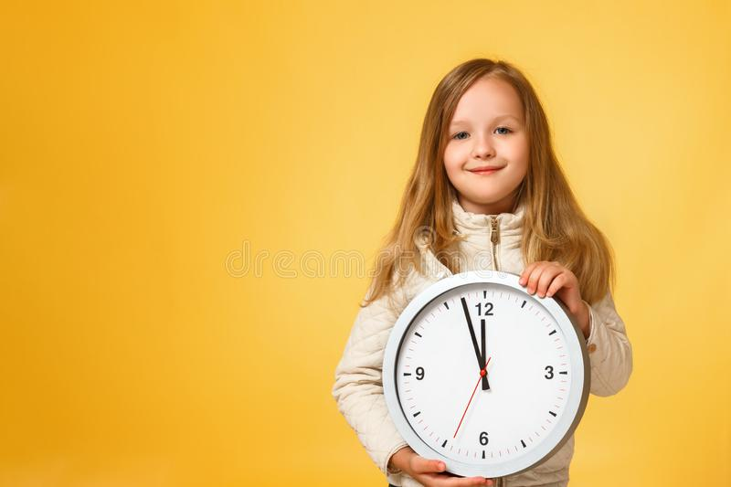 Cute little girl in a jacket holds a big clock on a yellow background. The concept of education, school, deadlines, time to study. Autumn. Copy space stock photo