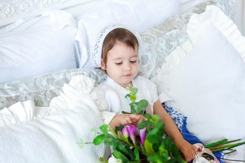 Cute little girl jumping on white bed stock image