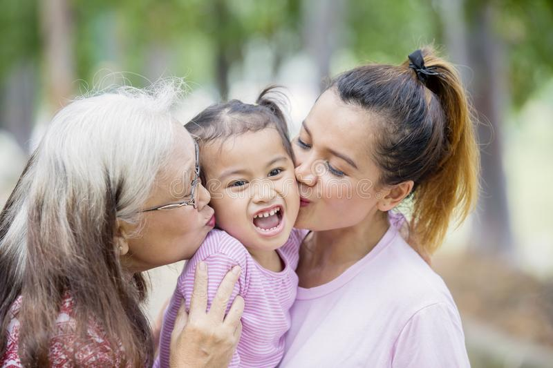 Cute little girl kissed by her mother and granny. Close up of cute little girl kissed by her mother and grandmother in the park royalty free stock photos