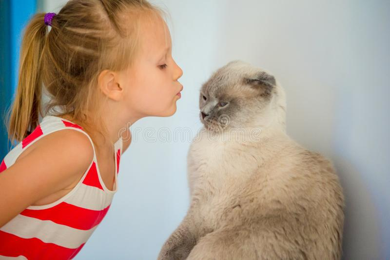 Cute little girl kissing her pet cat at home. Love between kid and pet royalty free stock photo