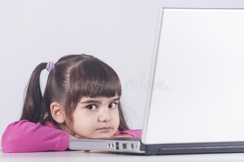 Cute little girl with laptop computer royalty free stock image