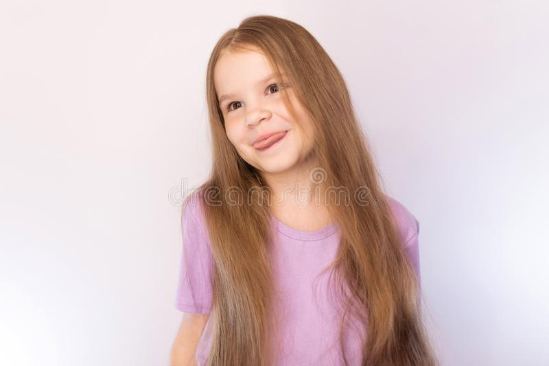 Cute little girl in a lavender shirt and with her hair, bowed his head to the side, shows the tongue on a light background stock photo