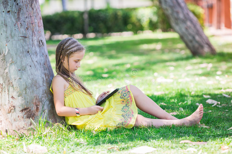 Cute little girl learning with tablet pc stock photography