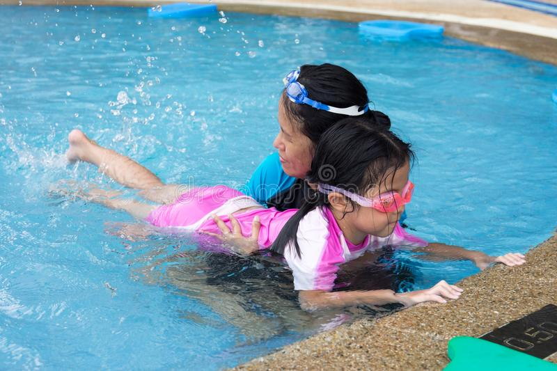 Cute little girl learning to swim with mother in swimming pool royalty free stock photos