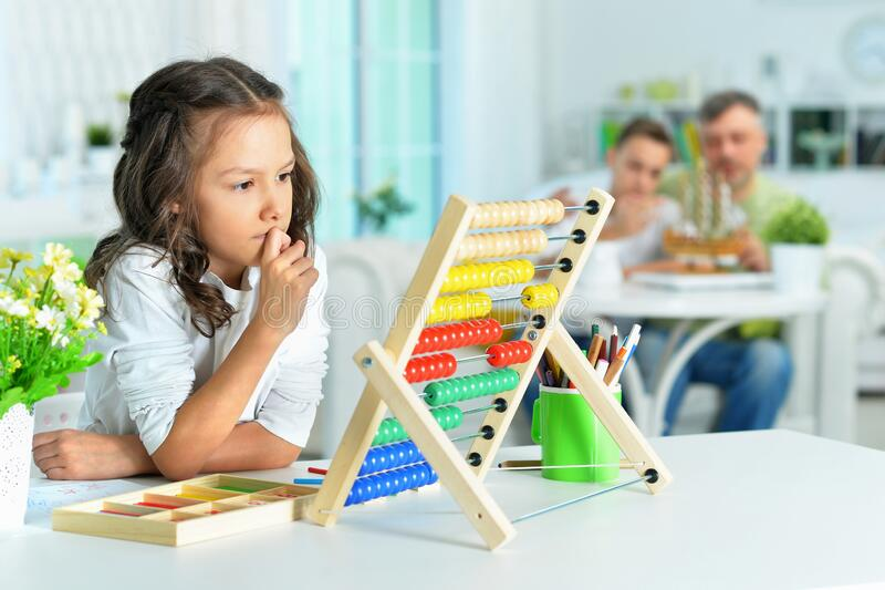 Cute little girl learning to use abacus royalty free stock photos