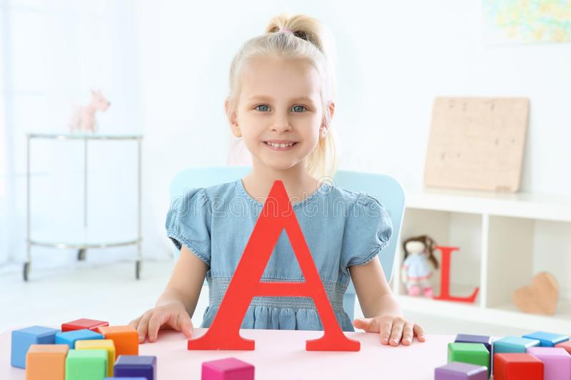 Cute little girl with letter A and colorful cubes royalty free stock image