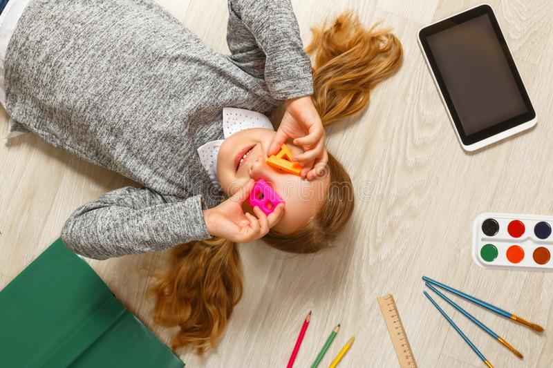 Cute little girl with letters A and B lying on the floor. A child is surrounded by a book, tablet, paints, brushes, pencils stock photography
