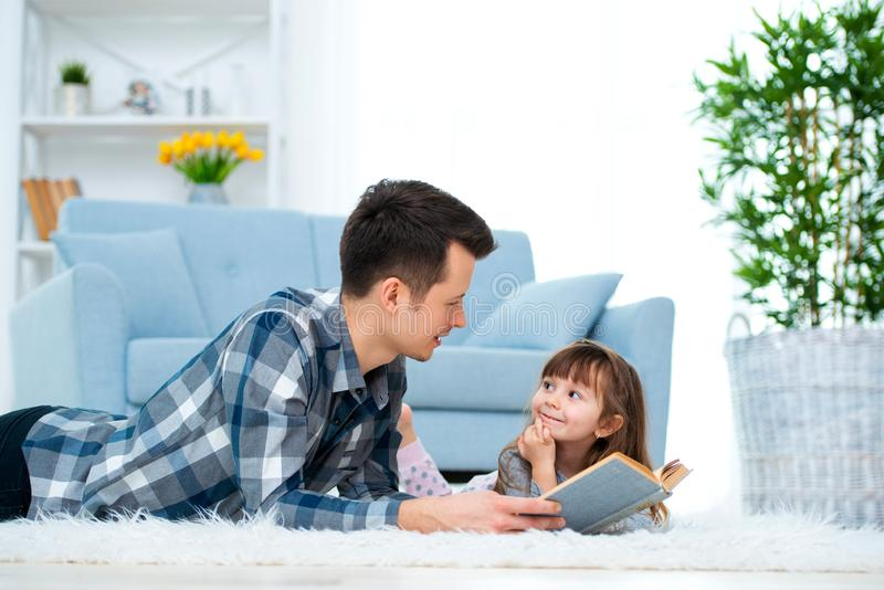 Cute little girl listening to dad reading fairy tale lying on warm floor together, caring father holding book , family hobbies royalty free stock photos