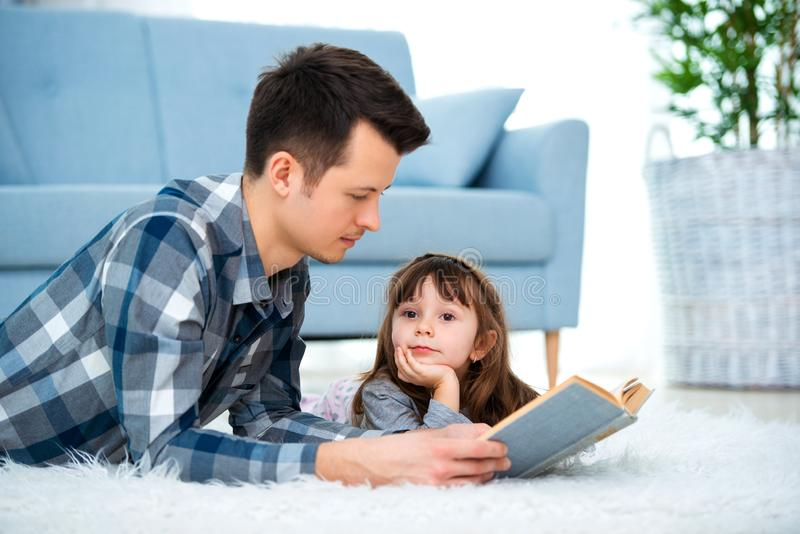 Cute little girl listening to dad reading fairy tale lying on warm floor together, caring father holding book , family hobbies stock photo
