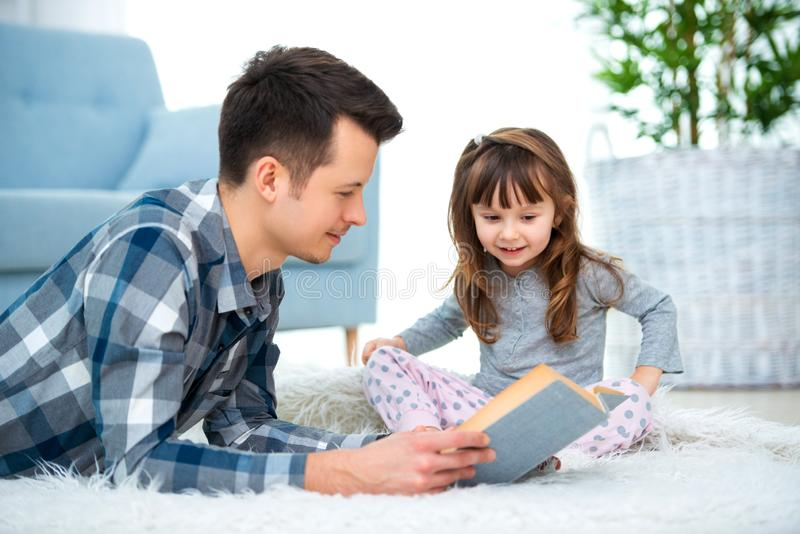 Cute little girl listening to dad reading fairy tale lying on warm floor together, caring father holding book , family hobbies stock photography