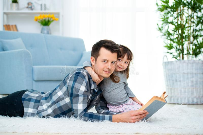 Cute little girl listening to dad reading fairy tale lying on warm floor together, caring father holding book , family hobbies stock images