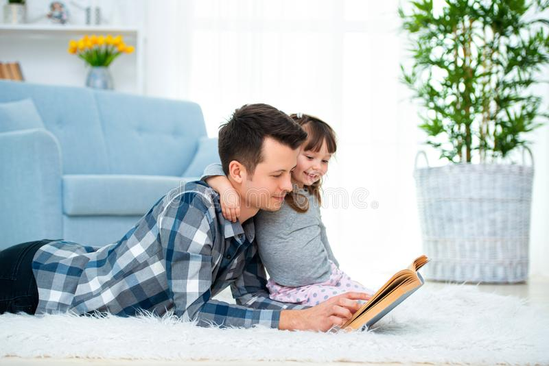 Cute little girl listening to dad reading fairy tale lying on warm floor together, caring father holding book , family hobbies stock photos