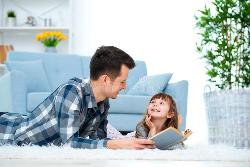 Cute little girl listening to dad reading fairy tale lying on warm floor together, caring father holding book , family hobbies royalty free stock images