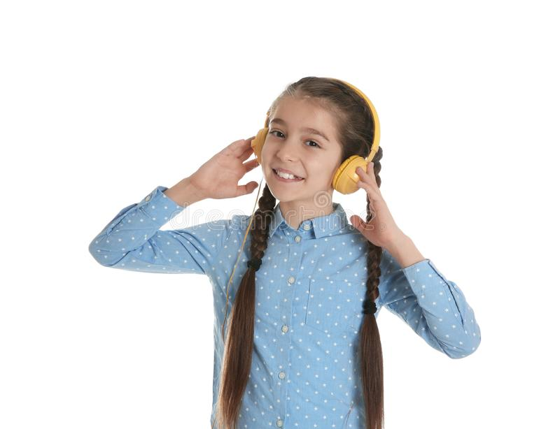 Cute little girl listening to music with headphones on white royalty free stock photography