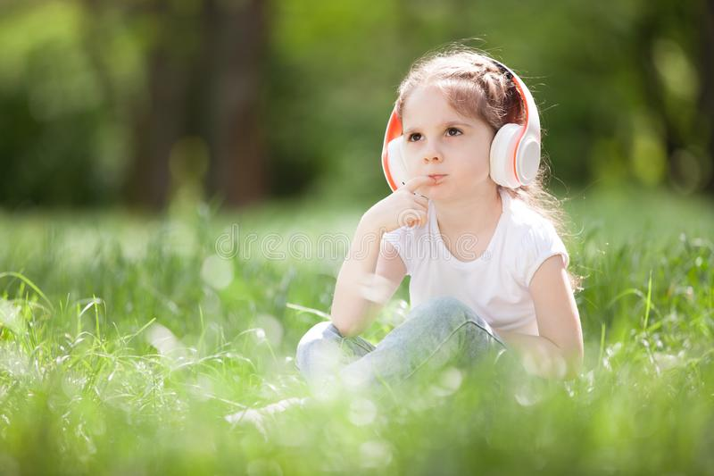 Cute little girl is listening to music in the park. Family outdoor lifestyle. Happy small kid in headphones sitting on green grass stock photo