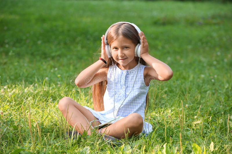 Cute little girl listening to music in park on summer day stock photo