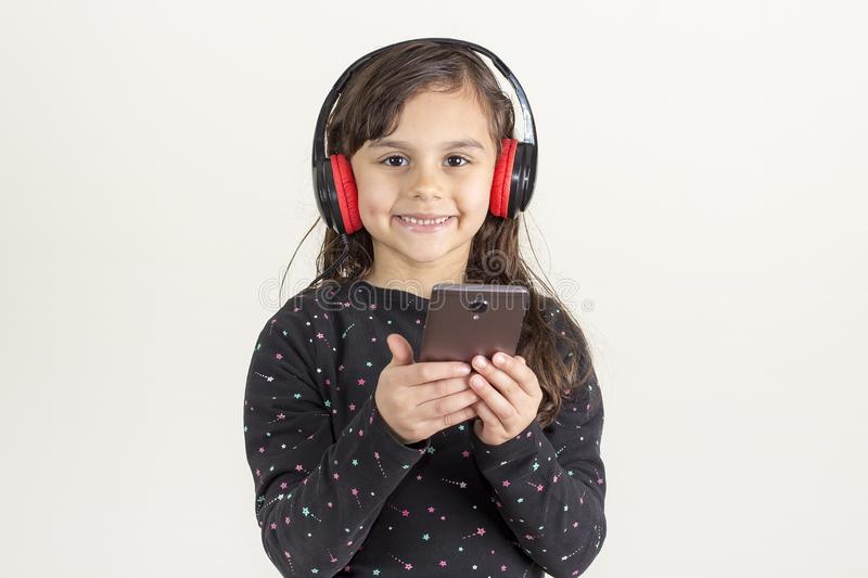 A cute little girl is listening to music using headphones stock image