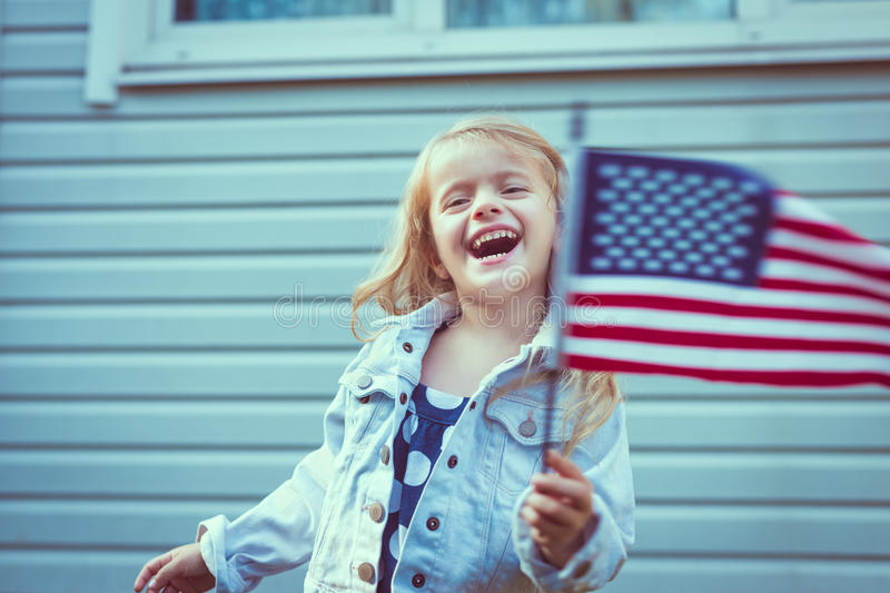 Cute little girl with long blond hair waving american flag. Cute little girl with long curly blond hair laughing and waving american flag. Independence Day, Flag royalty free stock photo
