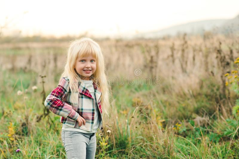 Cute little girl with long blonde hair and amazing eyes on nature background. Fashion stylish child outdoors. Happy and healthy stock photos
