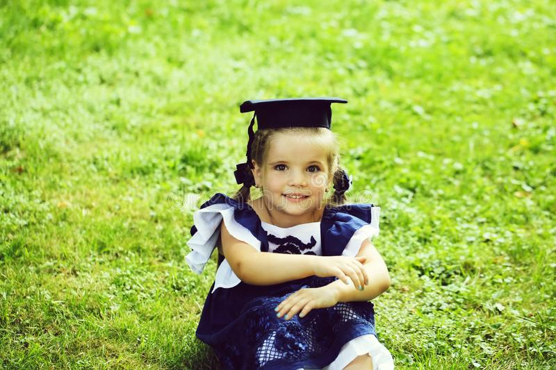 Cute little girl with long hair in black graduation cap. Cute little happy girl with long hair in black graduation cap or hat and blue dress sitting on green stock photo