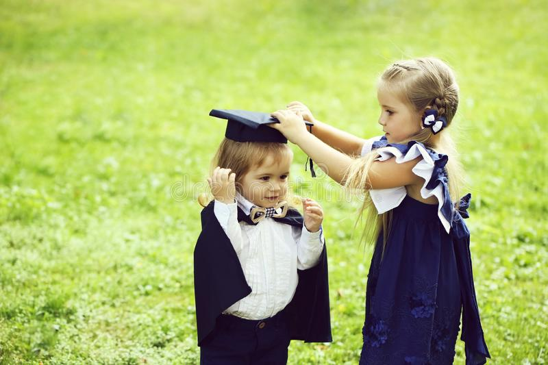 Cute girl dressing small boy in graduation hat and robe. Cute little girl with long hair in blue dress dressing adorable small boy in black graduation hat or cap royalty free stock photo