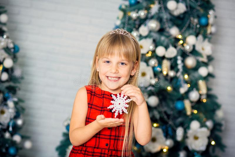 Cute little girl with long hair decorating christmas tree stock images