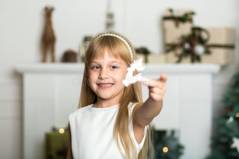 Cute little girl with long hair decorating christmas tree. Young kid in light bedroom with winter decoration. Happy family at home royalty free stock photo
