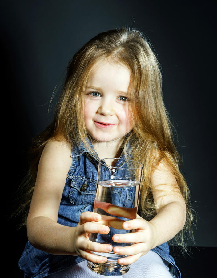 Cute little girl with long hair holding glass of water. Cute little girl with long hair holding transparent glass with clear water stock images