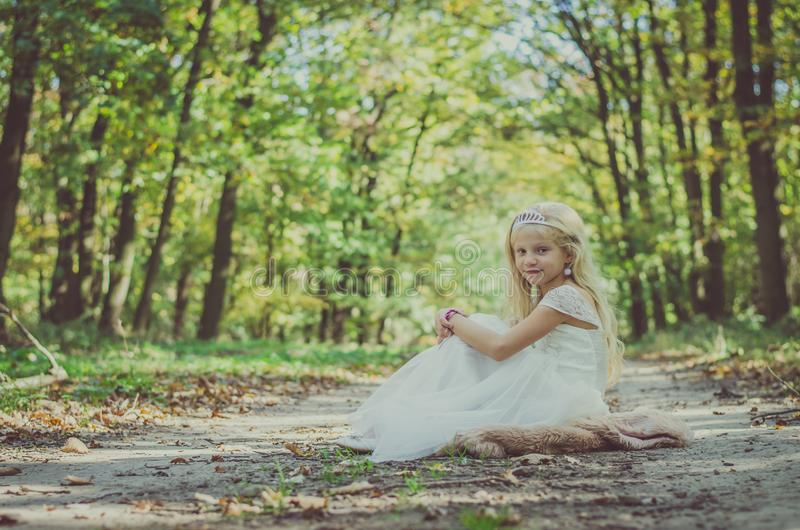 Romantic child sitting in princess dress under the trees stock photos