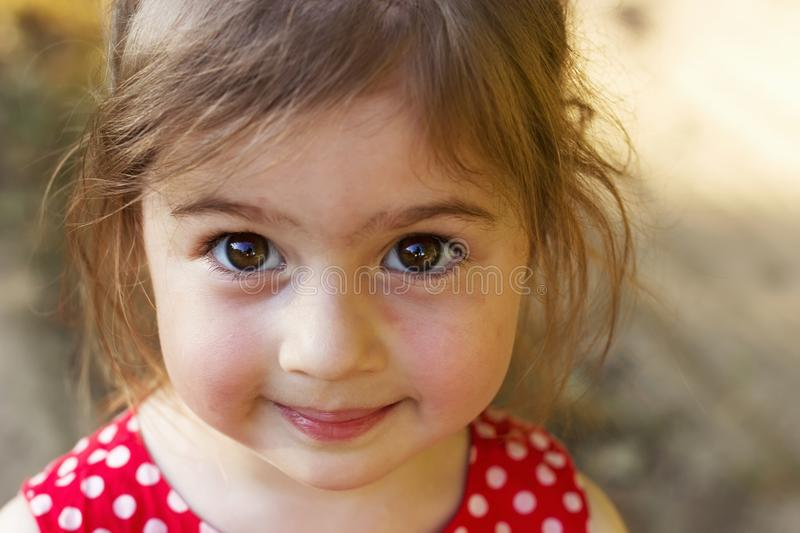 Cute little Girl looking at the camera surprised. Happy Kid out stock image