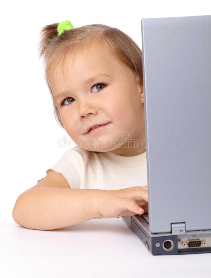 Cute little girl is looking out from her laptop stock image