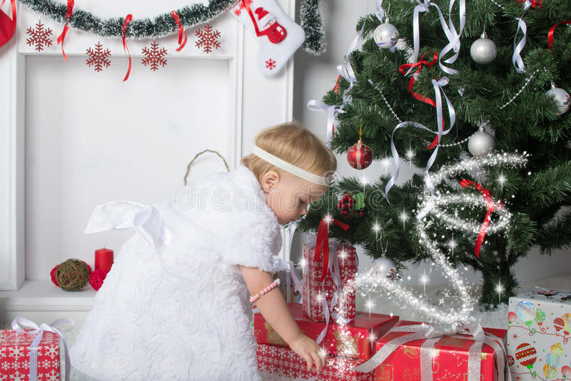 Cute little girl is looking for presents under Christmas New Yea stock image