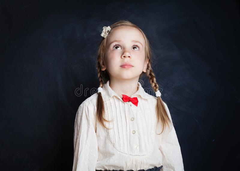 Cute little girl looking up on blackboard royalty free stock images