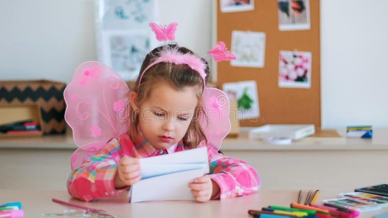 Cute little girl looks at pictures on art lesson royalty free stock images