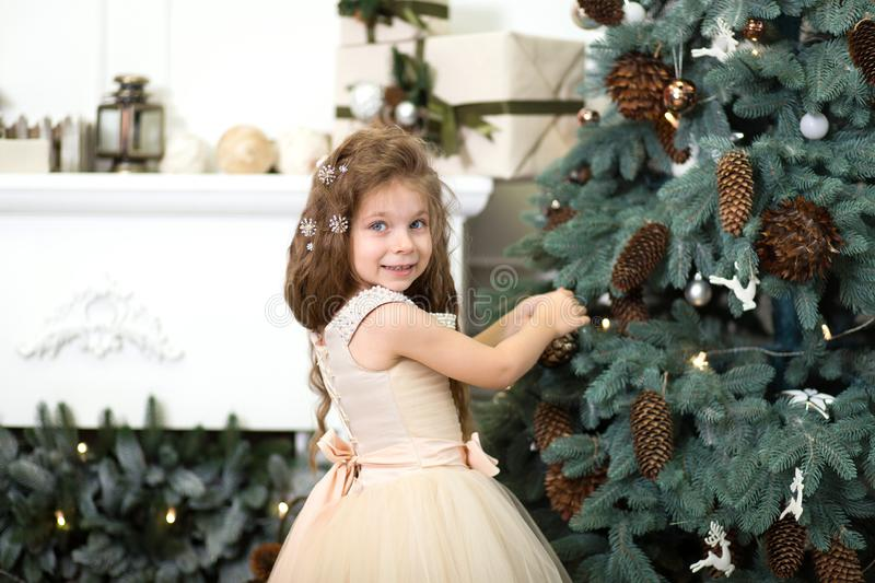 A cute little girl in a lush beige dress hangs cones on the Christmas tree that is standing in the house. Christmas tale, happy royalty free stock images