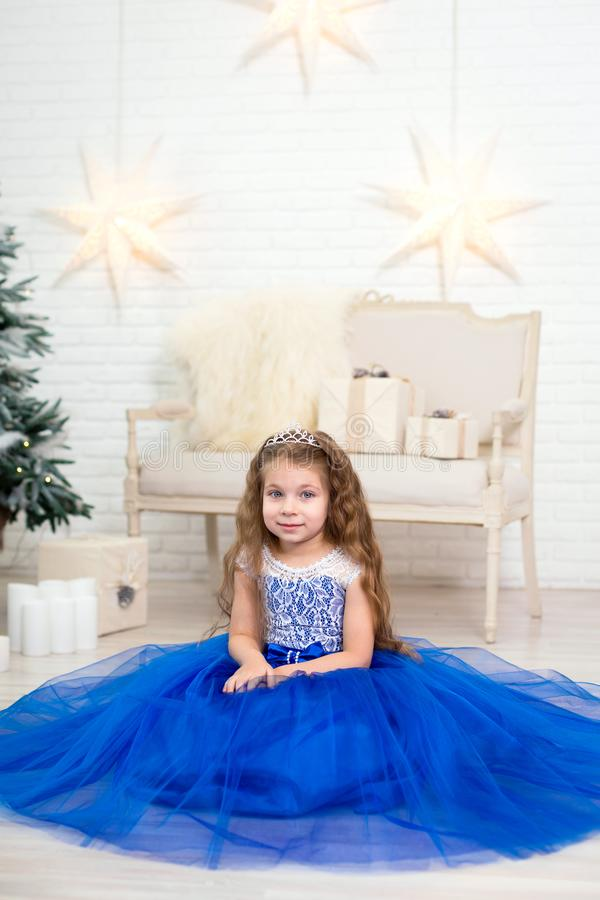 Cute little girl in a lush blue dress posing near the Christmas tree stock images