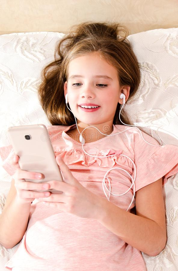 Cute little girl lying on the bed and listening to music using s royalty free stock image