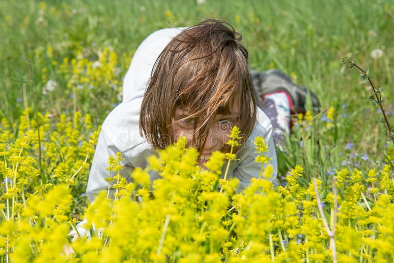 Cute little girl lying in the grass and flowers and laughing royalty free stock photo