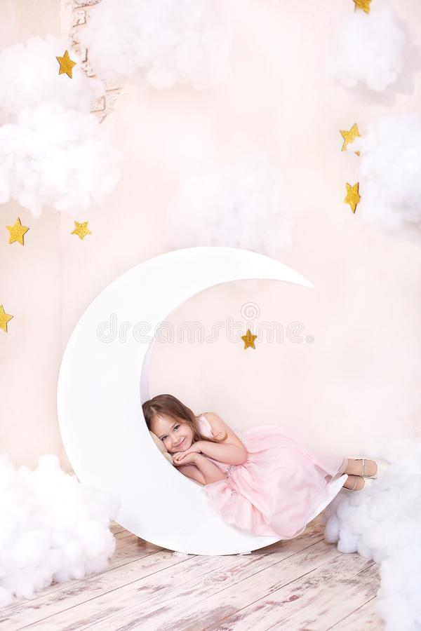 Cute little girl lying on the moon in anticipation of a miracle. Girl on the decorative moon on a background of stars. Sweet dream. S. The little girl dreams and royalty free stock photo