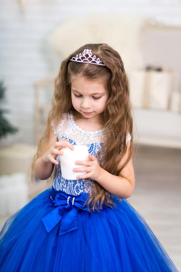 Cute little girl in a magnificent blue dress holding an artificial candle in her hands for home decoration on Christmas holidays. royalty free stock photos