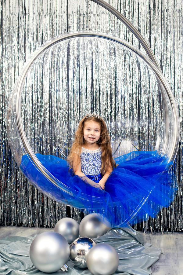 Cute little girl in a magnificent blue dress posing while sitting in a large glass ball chair royalty free stock photography