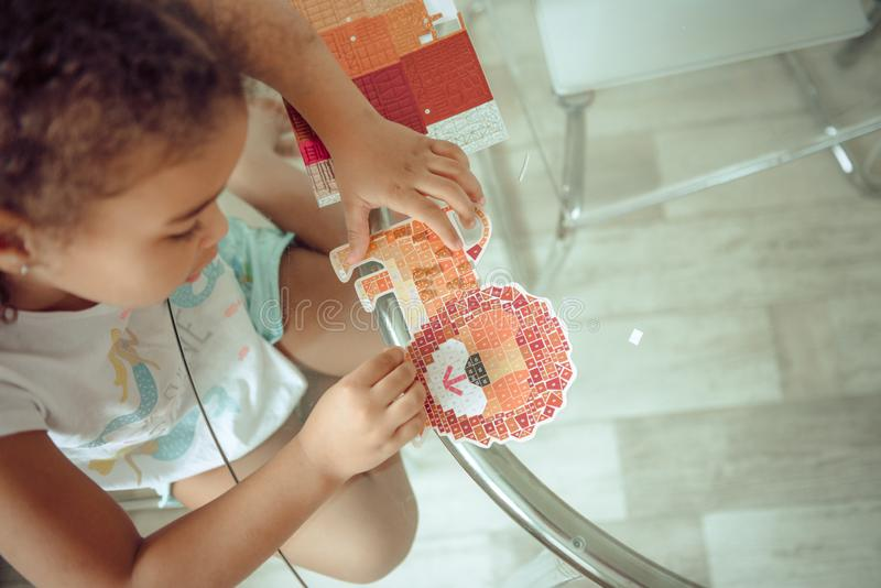 Cute little girl make applique, glues colorful house, applying a color paper using glue stick while doing arts and crafts in royalty free stock image