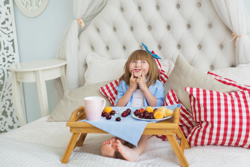 Cute little girl makes a faces on a bed in the morning stock photo